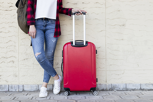 Woman with suitcase traveling after taking the ChooseFI Free Travel Course